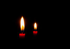 Burning red candles on black background Stock Photos