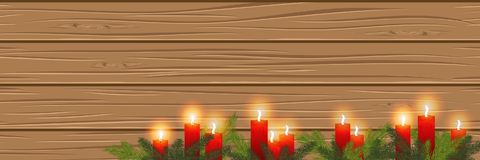 Burning candles on a wooden background. cosiness.Panorama. Vecto. Burning red candles in the branches of a Christmas tree, on a wooden background. Christmas card Royalty Free Stock Photo