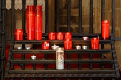 Burning red candles in a church, venice, italy. Red lit candles fill the frame with a darkened church interior in the background, santa maria del salute, venice royalty free stock photos