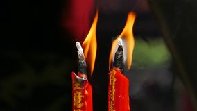 Burning of red candles. Two red candles burning in shrine of Chinese stock video footage