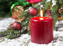Burning Red Christmas Candle. On a wood floor with snow Stock Photography