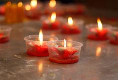 Burning red flower candle at chinese shrine for making merit in Royalty Free Stock Photos