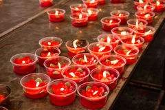 Burning red flower candle at chinese shrine for making merit in Stock Photos