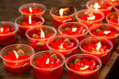 Burning red flower candle at chinese shrine for making merit in Stock Photography