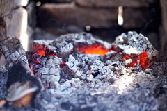 Burning red hot coals on the background of brick. Wall Royalty Free Stock Photos
