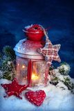Burning red lantern. Burning lantern in the snow at night stock photo