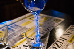 Burning sambuca. Poured into a glass from a glass stock image