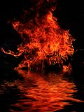 Burning shipwreck debris. Bright fire of burning shipwreck debris on the surface of the water stock images
