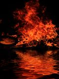 Burning shipwreck debris. Bright fire of burning shipwreck debris on the surface of the water stock photography