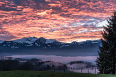 Burning Sky. Glowing clouds over foggy valley in front of mountainrange in Switzerland Royalty Free Stock Image