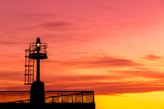 Burning sky at sunset. Burning sky at dawn with lighthouse silhouette royalty free stock photography