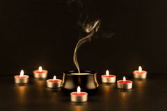 Burning small candles and one extinguished Stock Images