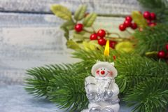 A burning snowman candle against the background of the Christmas tree branch. Theme of the New Year and Christmas Royalty Free Stock Images