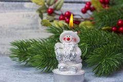 A burning snowman candle against the background of the Christmas tree branch. Theme of the New Year and Christmas Stock Photo