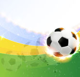 Burning soccer ball on playing field. Soccer ball illuminated by spotlights on a green background. Abstract sports background Stock Image