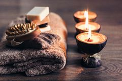 Burning spa aroma candles in coconut shell, handmade soap, towel and washcloth, spa concept background.  stock photo