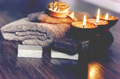 Burning spa aroma candles in coconut shell, handmade soap, towel and washcloth, spa concept background.  stock photography