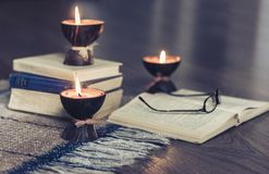 Burning spa aroma candles in coconut shell, plaid, glasses and books, cozy home interior background royalty free stock photo