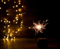 Burning sparkler and christmas lights on wooden background Royalty Free Stock Photography