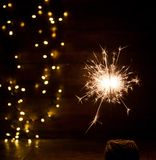 Burning sparkler and christmas lights on wooden background Stock Images