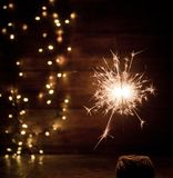 Burning sparkler and christmas lights on wooden background Royalty Free Stock Photo