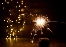 Burning sparkler and christmas lights on wooden background Royalty Free Stock Images