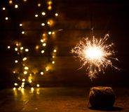 Burning sparkler and christmas lights on wooden background Stock Photo