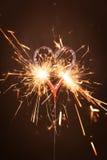 Burning sparkler in heart shape. Against black background Stock Photos