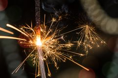Burning sparkler with sparks bursting in air. stock image