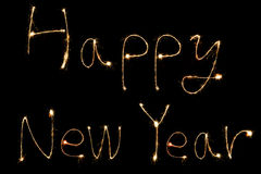Burning sparkler stick and writing happy new year words Stock Images
