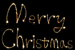 Burning sparkler stick and writing Merry Chistmas sparkling word Stock Photo
