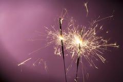 Burning sparklers on pink background Stock Image