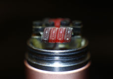 Burning staple staggered fused clapton coil in rebuildable dripping atomizer Stock Image