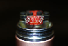 Burning staple staggered fused clapton coil in rebuildable dripping atomizer Royalty Free Stock Photo