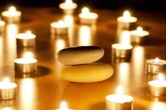 Burning stearinljus och pebbles för aromatherapy Arkivfoto