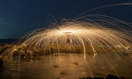 Burning steel wool. Amazing steel wool coast the sea on the beach in sunset time stock images