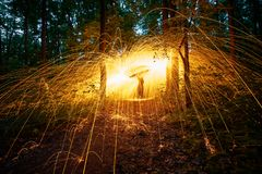 Burning steel wool spinned in the forest. Showers of glowing sparks from spinning steel wool Royalty Free Stock Photo