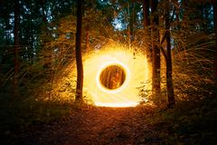 Burning steel wool spinned in the forest. Showers of glowing sparks from spinning steel wool Stock Photos