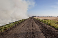 Burning stubble. Smoke from  burning stubble in a farm field adjacent to a dirt road Royalty Free Stock Images