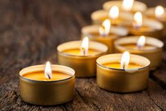 Burning tea candles on the background of old wooden planks stock photo
