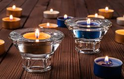 Burning tea candles on the background of old wooden planks stock image