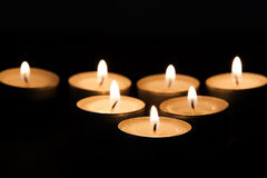 Burning tealights in darkness Royalty Free Stock Photos