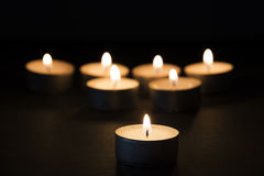 Burning tealights in darkness Royalty Free Stock Photography