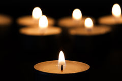 Burning tealights in darkness Stock Images