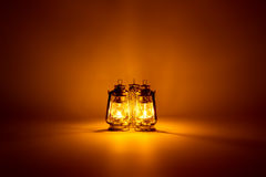 Burning three kerosene lamps background Stock Photography