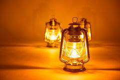 Burning three kerosene lamps, gold light Stock Image
