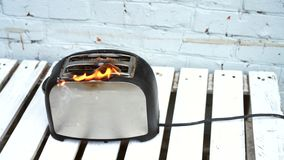 Burning toaster. Toaster with two slices of toast caught on fire over white background. Danger of careless handling of electrical appliances. Fire stock video footage