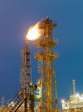 Burning torch and industrial tower. Of metal on a chemical plant at night royalty free stock image