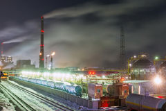 Burning torch and industrial tower. Railway tank and and industrial tower of metal on a chemical plant at night stock image