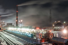 Burning torch and industrial tower. Railway tank and and industrial tower of metal on a chemical plant at night stock photography